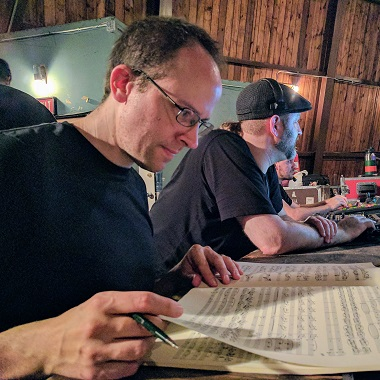 Photo of Kevin Stahl reading a score at a recording session